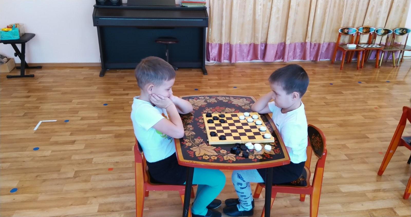 Юные спортсмены участвуют в турнире по шашкам.